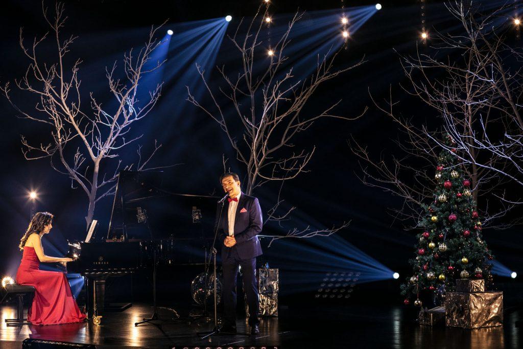 Scena oświetlona delikatnym światłem. Przed mikrofonem stoi mężczyzna w garniturze. Obok, przy fortepianie siedzi kobieta w czerwonej sukni. Za nimi kilka drzew bez liści. Po prawej stronie stoi choinka z bombkami. Pod nią pudełka opakowane w złoty papier.