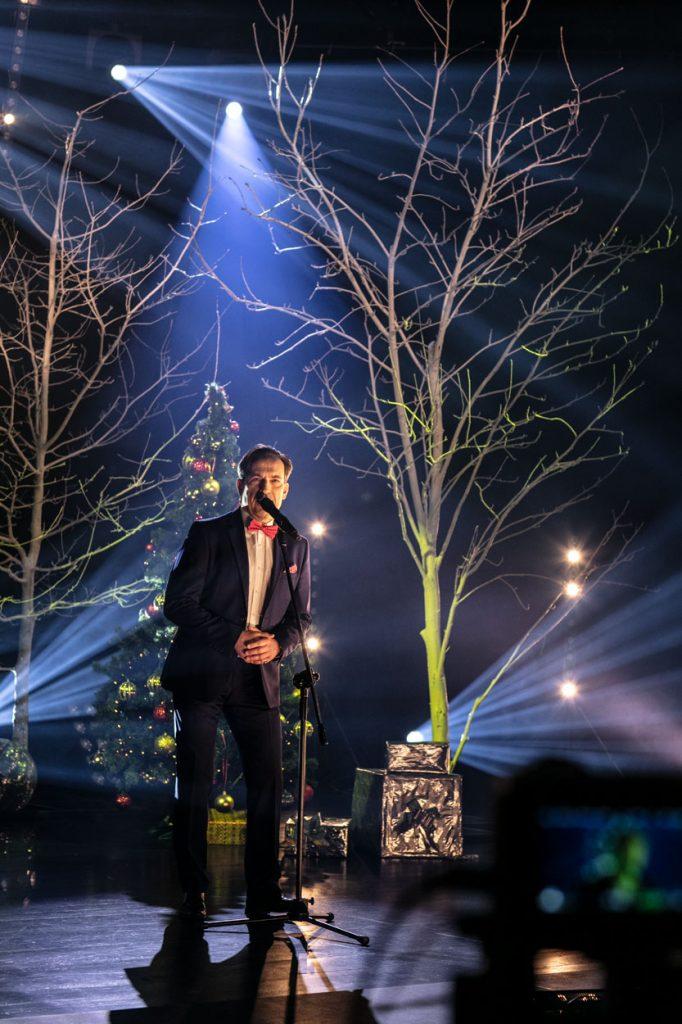 Scena oświetlona delikatnymi łunami świateł. Na środku stoi mężczyzna w garniturze. Przed nim na statywie mikrofon. Za nim drzewa bez liści i choinka z bombkami.