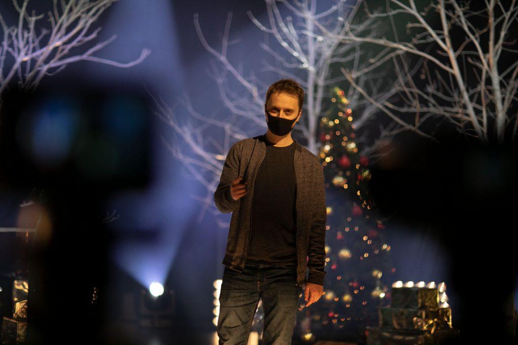 Scena w półmroku. Widoczne białe łuny od reflektorów. Mężczyzna w maseczce ochronnej, w swetrze, stoi na środku sceny. Za nim choinka i gałęzie drzew bez liści.