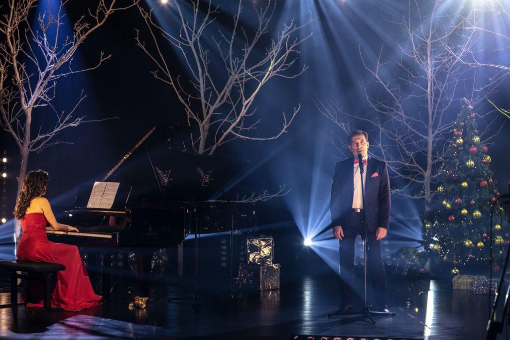 Scena oświetlona delikatnymi łunami białego światła. Na niej, przed statywem z mikrofonem stoi mężczyzna w garniturze. Po lewej stronie stoi fortepian, na nim otwarte nuty. Przy fortepianie siedzi kobieta w czerwonej sukni. Za nimi stoi kilka drzew bez liści. W kilku miejscach leżą pudełka opakowane złotym papierem. Po prawej stronie choinka z bombkami.