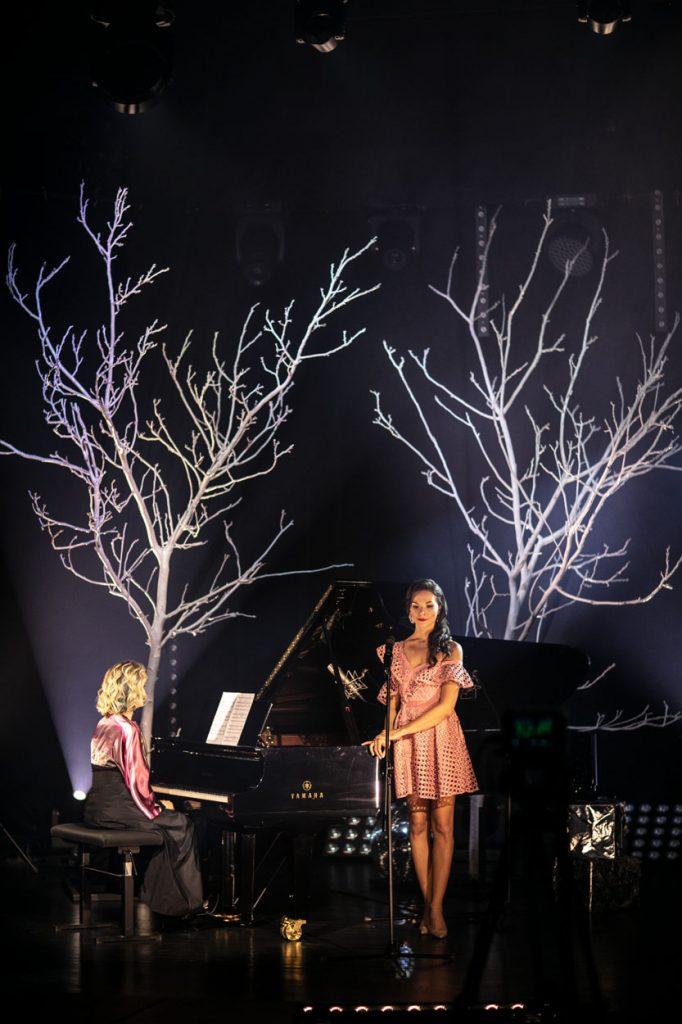 Scena w półmroku. Na niej dwie kobiety, jedna siedzi przy fortepianie. Druga stoi obok. Za fortepianem dwa drzewa bez liści, podświetlone białym światłem.