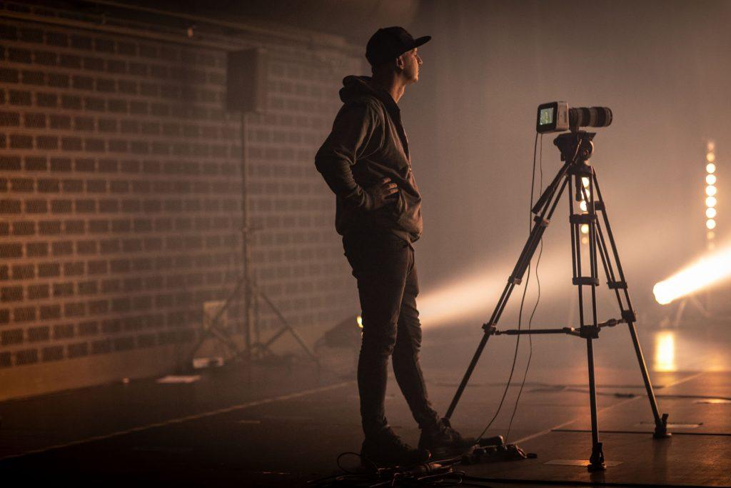 Scena w półmroku. Na środku stoi mężczyzna w sportowej bluzie i czapeczce z daszkiem. Przed nim, na statywie jest aparat. W głębi widać łunę białego światła z reflektora stojącego na ziemi.