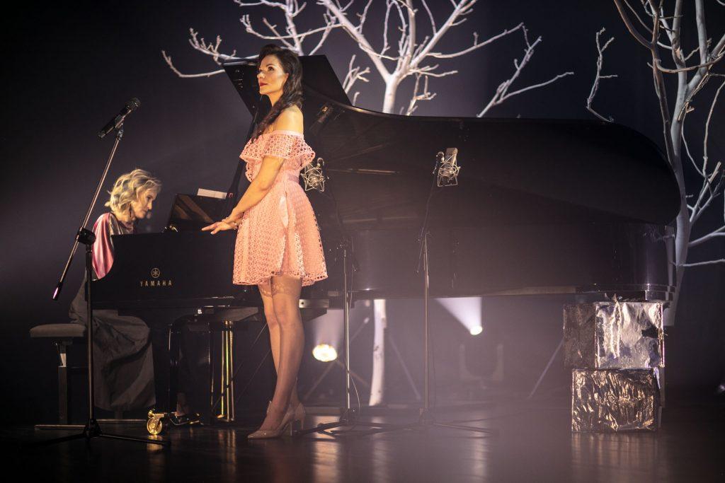 Scena w półmroku. Na niej dwie kobiety, jedna siedzi przy fortepianie. Druga stoi obok. Za nią leżą dwa pudełka zapakowane w złoty papier. Za fortepianem dwa drzewa bez liści, podświetlone białym światłem.