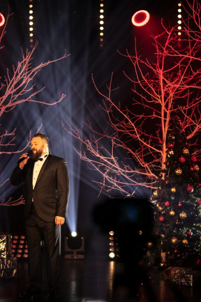 Scena oświetlona czerwono-białym światłem. Na scenie mężczyzna w garniturze. Śpiewa, trzymając mikrofon w ręku. Za nim podświetlone na czerwono gałęzie drzew. Z boku stoi choinka z bombkami.