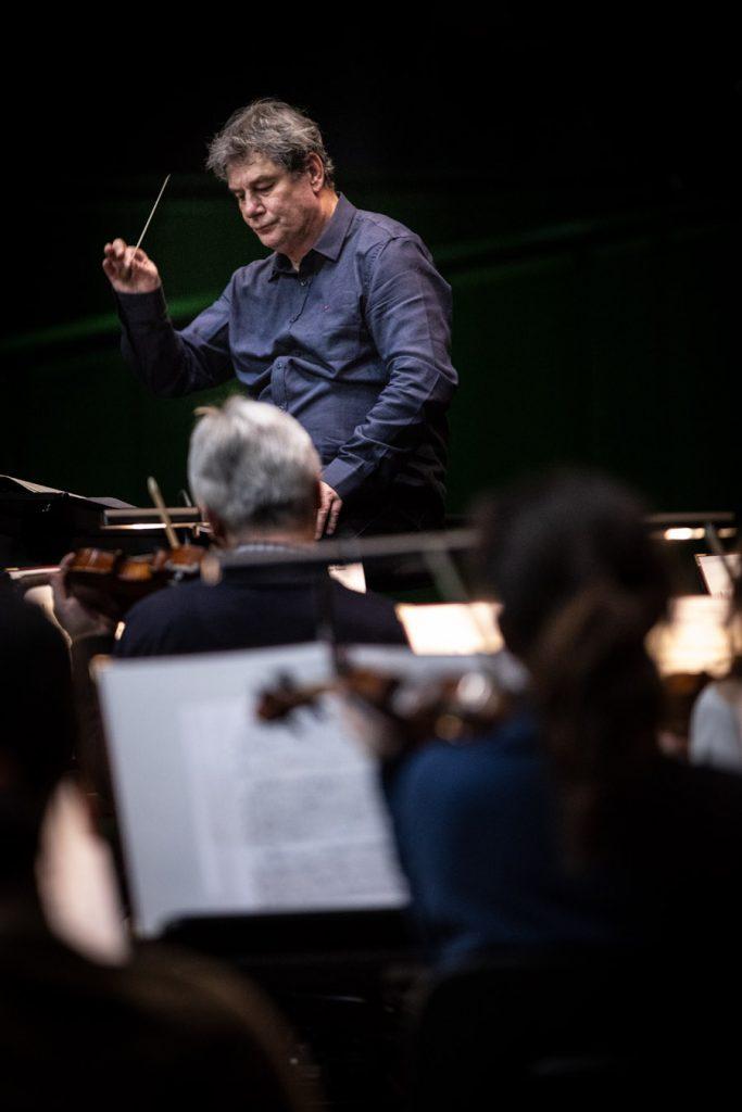 Tyłem, przy pulpitach, siedzi kilku muzyków orkiestry. Przed nimi stoi dyrygent. W uniesionej ręce trzyma batutę.
