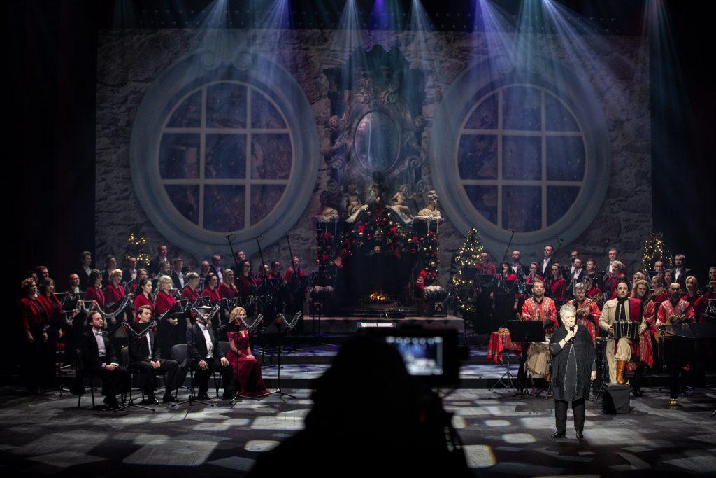 Na scenie soliści i Chór Opery i Filharmonii Podlaskiej. Po prawej stronie stoi z mikrofonem dyrektor opery Prof. Violetta Bielecka. Za nią muzycy w strojach argentyńskich. Po lewej stronie siedzą soliści. Pośrodku sceny stoi duży kominek w którym pali się ogień.