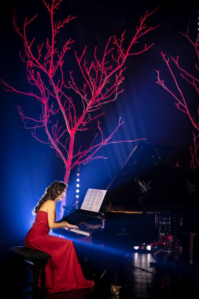 Scena oświetlona na niebiesko. Przy fortepianie siedzi kobieta w czerwonej sukni. Za nią gałęzie drzew bez liści, podświetlone na czerwono.
