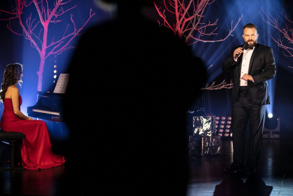 Po lewej stronie kobieta w czerwonej sukni siedzi przy fortepianie. Po prawej stronie stoi mężczyzna w garniturze stoi z mikrofonem w ręku. Za nimi drzewa bez liści podświetlone na czerwono. Na środku kadru czarna plama.