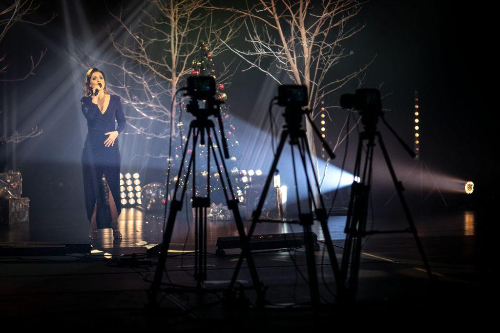Scena podświetlona łunami białego światła. Na scenie kobieta w granatowej sukni. Za nią drzewa bez liści podświetlone na biało. Z przodu trzy aparaty na statywach.