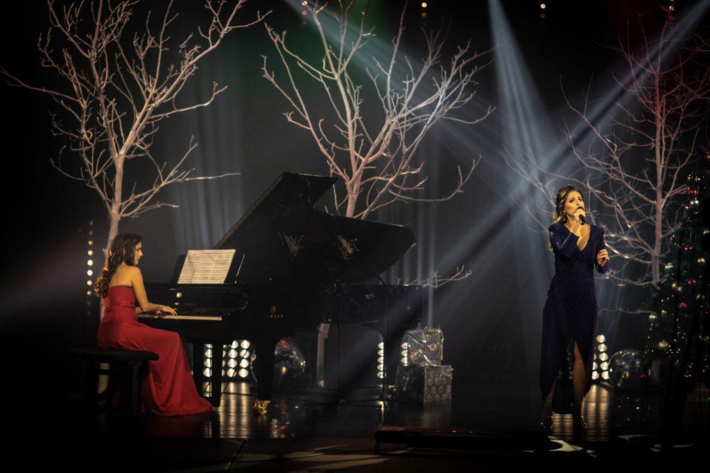 Na scenie dwie kobiety. Jedna w czerwonej sukni, siedzi przy fortepianie. Druga, w granatowej sukni, stoi z mikrofonem w ręku. Za nimi drzewa bez liści podświetlone na biało. Pomiędzy nimi łuny jasnego światła. Przy fortepianie pudełka opakowane w złoty papier.