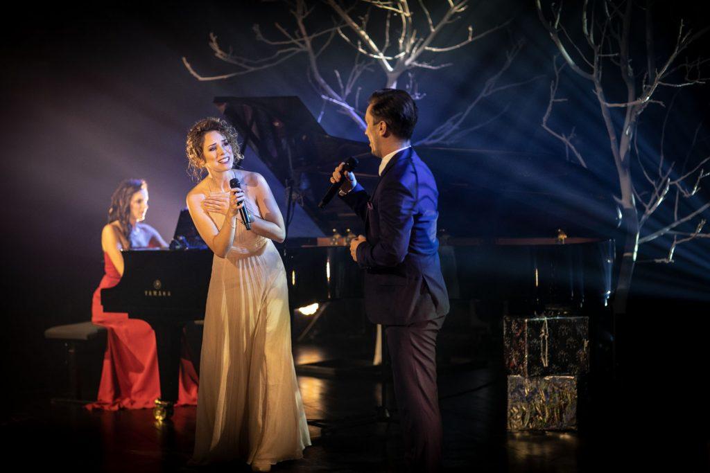 Scena słabo oświetlona. Na środku kobieta w jasnej sukni i mężczyzna w garniturze śpiewają do mikrofonu. Za nimi, przy fortepianie siedzi kobieta. Dalej widać gałęzie drzew bez liści, podświetlone jasnym światłem.