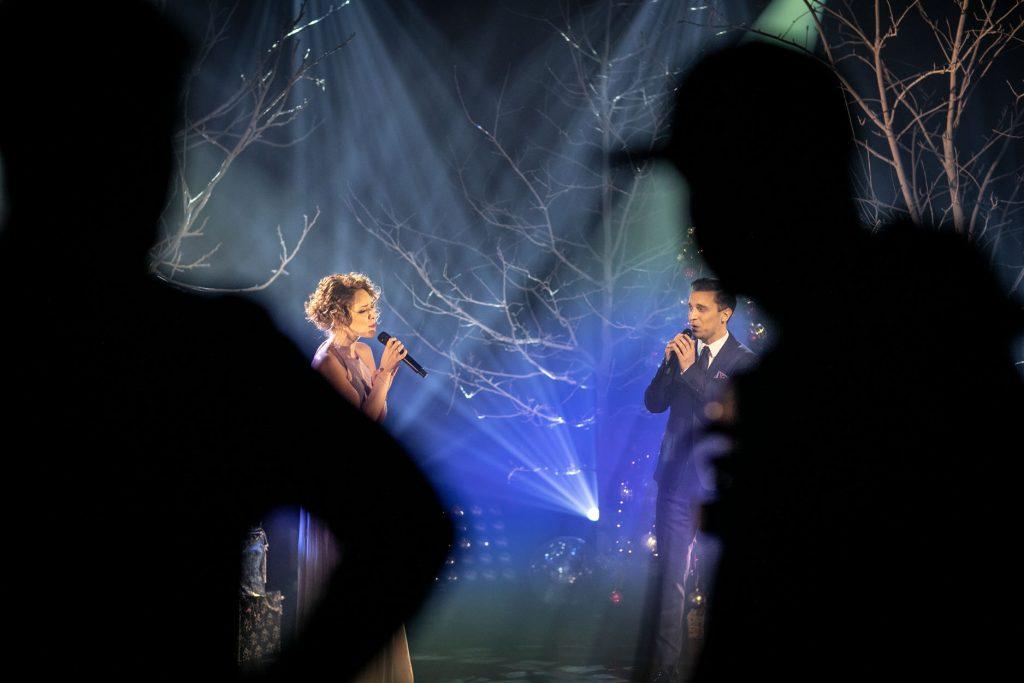 Scena podświetlona na biało-niebiesko. Na niej śpiewają do mikrofonu kobieta i mężczyzna. Z przodu widoczne cienie dwóch osób.