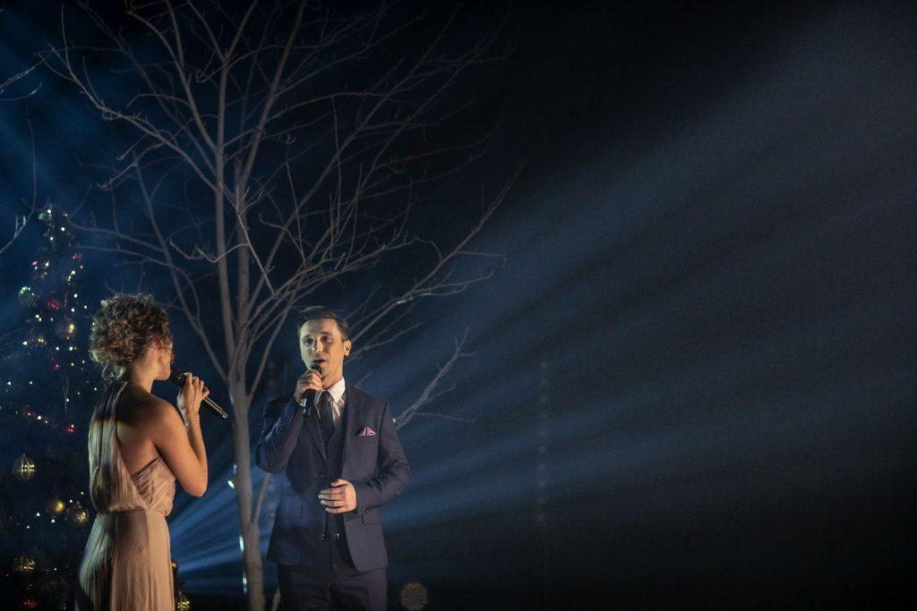 Na scenie półmrok. Widoczne smugi jasnego światła. Kobieta i mężczyzna śpiewają do mikrofonów. Za nimi drzewa bez liści.