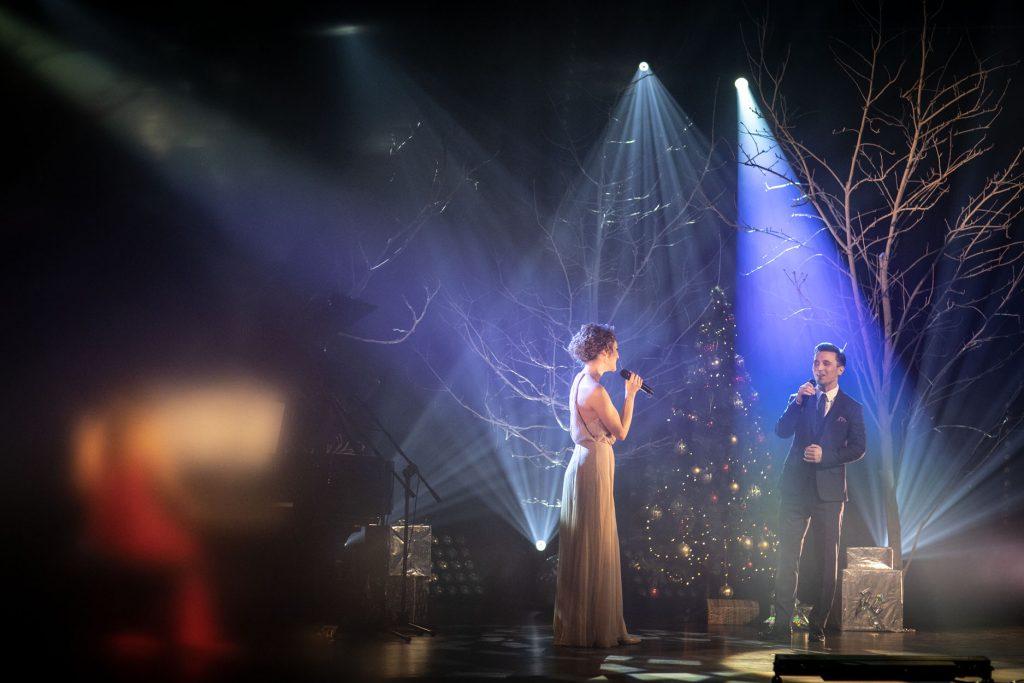 Kilka reflektorów, łuną białego światła, oświetla scenę. Na środku stoi kobieta w jasnej sukni i mężczyzna w garniturze. Śpiewają do mikrofonu. Za nimi stoi choinka z bombkami. Na scenie stoi kilka drzew bez liści. Pod nimi pudełka opakowane w złoty papier.