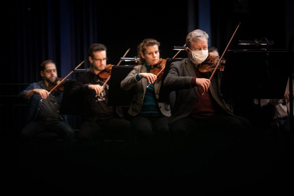 Próba do koncertu. Czterech muzyków orkiestry gra na skrzypcach.