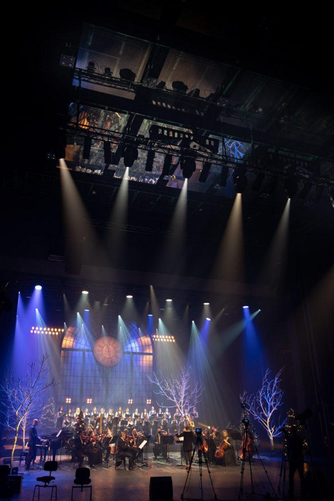 Widok na scenę z końca widowni. Na środku siedzi orkiestra. Za nią stoi chór. Z góry oświetla scenę na niebiesko kilkanaście reflektorów. Z przodu sceny stoją aparaty na statywach.