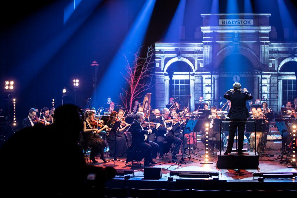 Na scenie gra orkiestra Opery. Na środku, na podeście, z uniesionymi rękami stoi dyrygent. W oddali scenografia przedstawiająca budynek z dużymi, zaokrąglonymi oknami. Na środku wisi zegar. Na samej górze widoczny napis ''Białystok''.