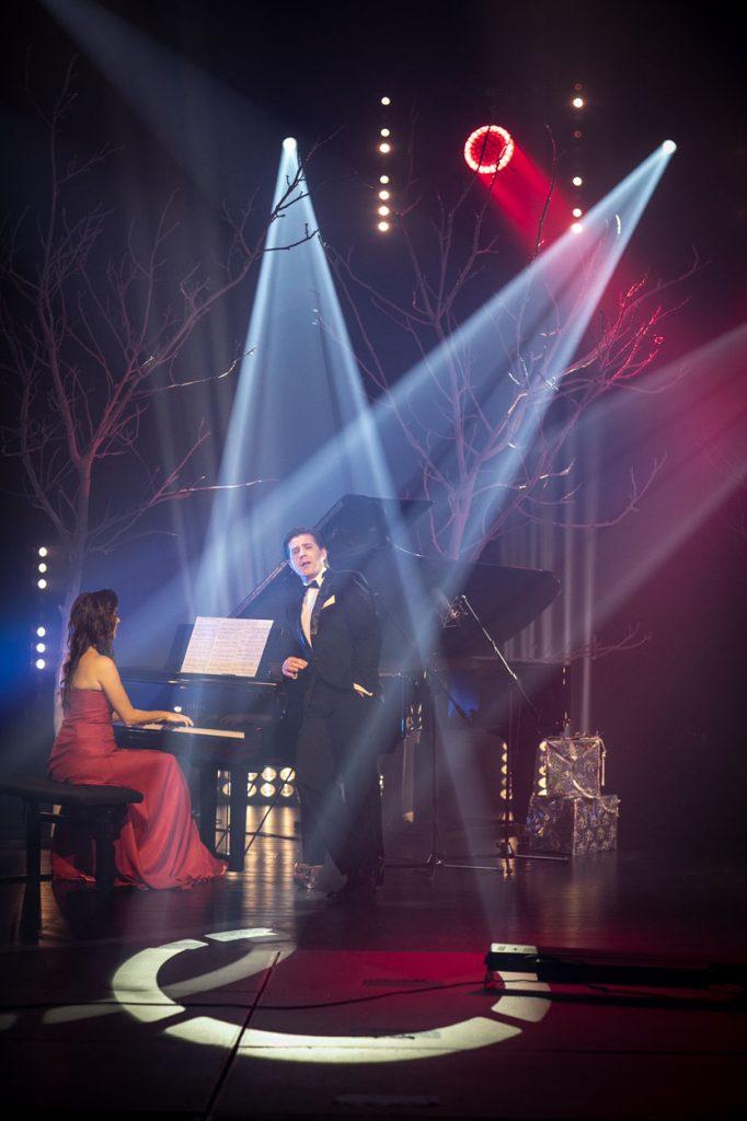 Na środku stoi fortepian. Przy nim siedzi kobieta. Obok , oparty o niego stoi mężczyzna w garniturze. Z góry oświetlają scenę białym światłem dwa reflektory.