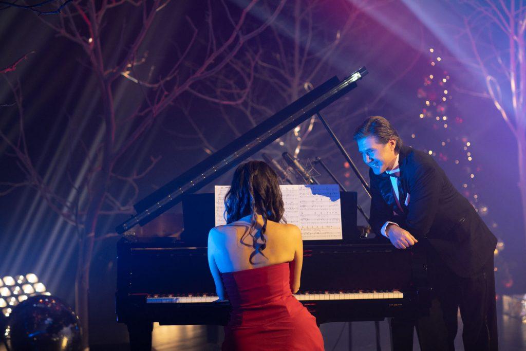 Przy fortepianie siedzi kobieta w czerwonej sukni. Obok, oparty o niego stoi mężczyzna w garniturze. Z tyłu widoczne gałęzie drzew bez liści. Na nich widać smugi jasnego światła. W tle świecąca choinka.