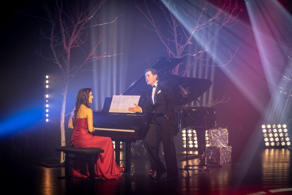 Kobieta siedząca przy fortepianie, patrzy na mężczyznę stojącego tuż obok. Przy fortepianie stoją pudełka opakowane w złoty papier. Dalej stoją drzewa bez liści, na które padają smugi jasnego światła. Na ziemi rozstawione reflektory świecące białym światłem.