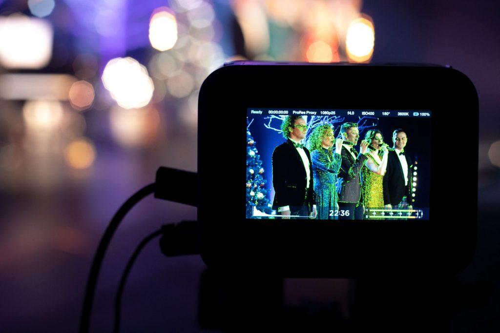 Na zdjęciu widoczny monitor. Na nim wyświetla się kadr z koncertu. Pięć osób stoi obok siebie. Troje z nich śpiewa do mikrofonu.
