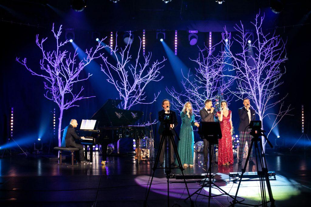 Scena oświetlona na niebiesko. Na środku stoi pięciu solistów. Dwie kobiety w długich sukniach i trzech mężczyzn. Wszyscy śpiewają do mikrofonu. Obok mężczyzna gra na pianinie. Za nimi drzewa bez liści podświetlone na biało..