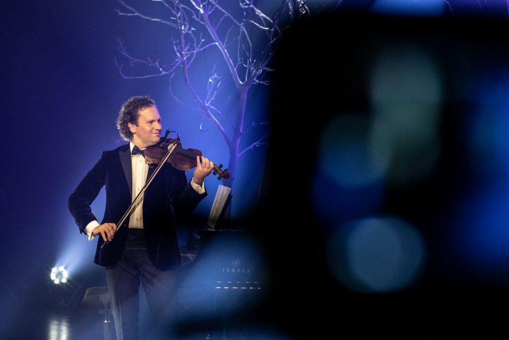 Scena oświetlona na niebiesko. Mężczyzna w garniturze gra na skrzypcach, uśmiechając się. Za nim widać gałęzie drzew bez liści.