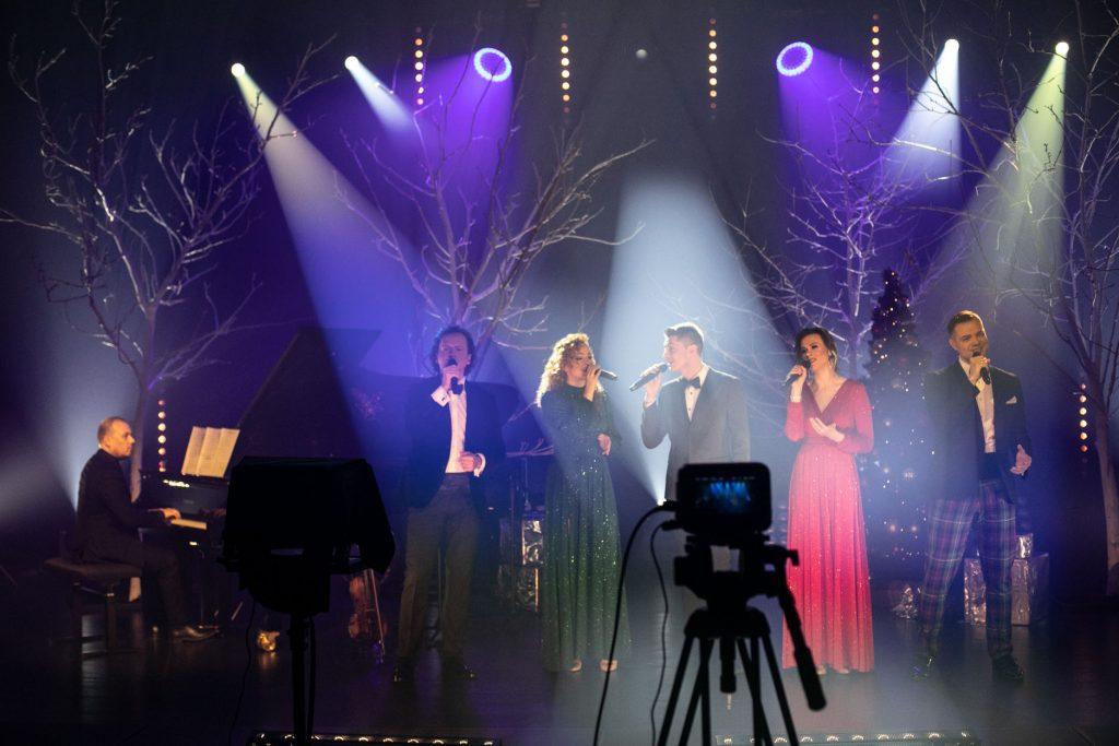 Scena oświetlona na niebiesko. Na środku stoi pięciu solistów. Dwie kobiety w długich sukniach i trzech mężczyzn. Wszyscy śpiewają do mikrofonu. Obok mężczyzna gra na pianinie. Za nimi drzewa bez liści w smugach jasnego światła. Z przodu widoczny aparat na statywie.