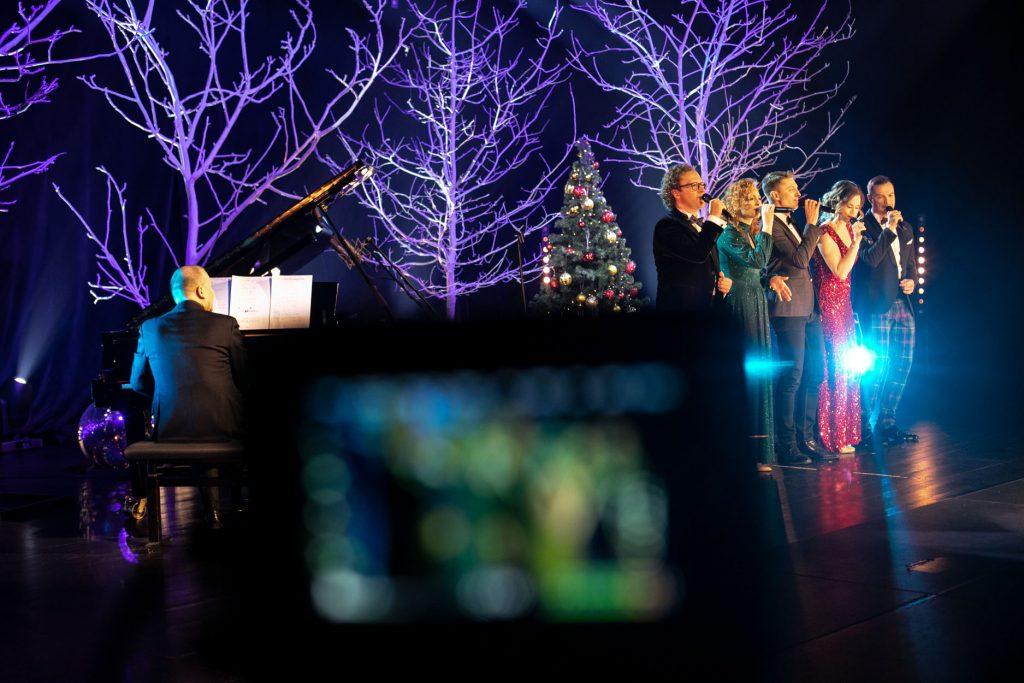 Scena oświetlona na niebiesko. Na środku stoi pięciu solistów. Dwie kobiety w długich sukniach i trzech mężczyzn. Wszyscy śpiewają do mikrofonu. Obok mężczyzna gra na pianinie. Za nimi drzewa bez liści podświetlone na biało. Pomiędzy nimi choinka z bombkami.