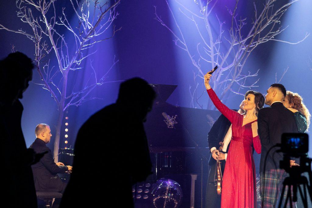 Dwie kobiety i dwóch mężczyzn pozuje do zdjęcia. Kobieta w czerwonej sukni trzyma telefon w górze. Po lewej stronie mężczyzna siedzi przy fortepianie. Za nimi widoczne gałęzie drzew bez liści. Z przodu widoczne cienie dwóch ośób.