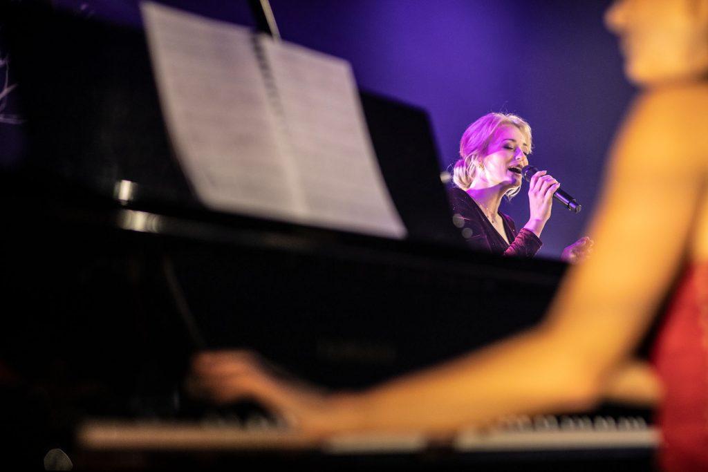 Na zdjęciu widoczna część fortepianu na którym gra kobieta w czerwonej sukni. Dalej widać kobietę śpiewającą do mikrofonu.