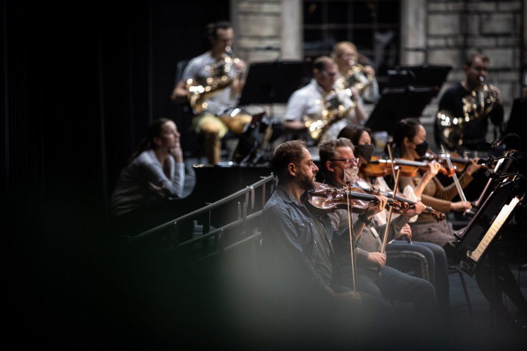 Zdjęcie zrobione z boku. W jednym rzędzie siedzą cztery osoby grające na skrzypcach. Większość ma na twarzy maseczki ochronne. Dalej widać kilku muzyków grających na instrumentach dętych.