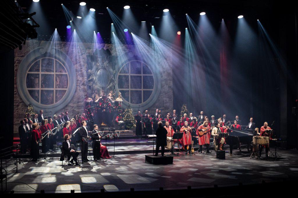 Koncert ''Siła serc''. Na scenie po obydwu stronach chór opery. Z przodu po prawej stronie muzycy z zespołu ''Sierra Manta'' w argentyńskich strojach. Po lewej stronie soliści. Na środku dyrygent i kierownik chóru - Prof. Violetta Bielecka. Z tyłu widać duży kominek w którym pali się ogień. Dookoła ozdobiony jest bombkami.