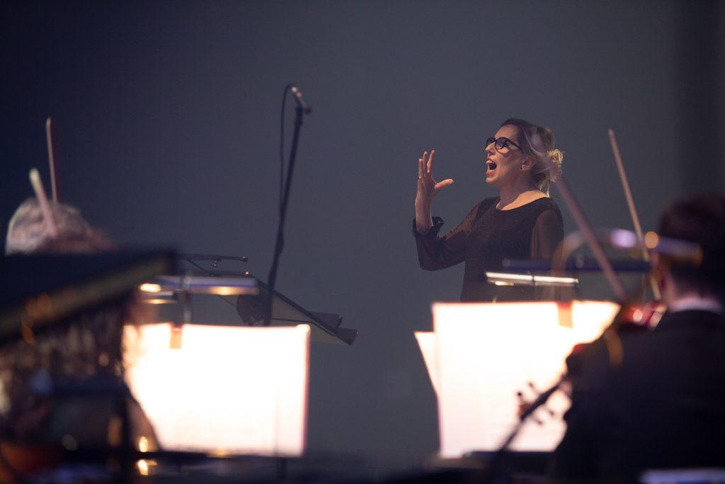 Z przodu rozmyte pulpity z nutami. Za nimi kobieta z uniesioną ręką i otwartą buzia. Przed nią mikrofon na statywie.