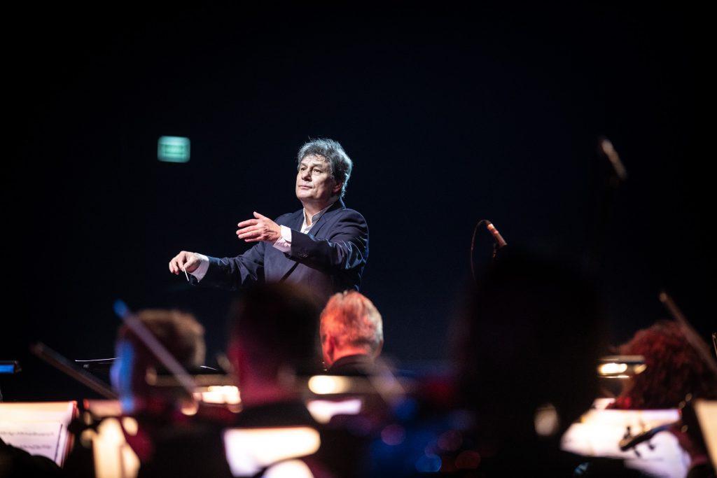 Dyrygent trzymający batutę, stoi z uniesionymi rękoma przed orkiestrą.