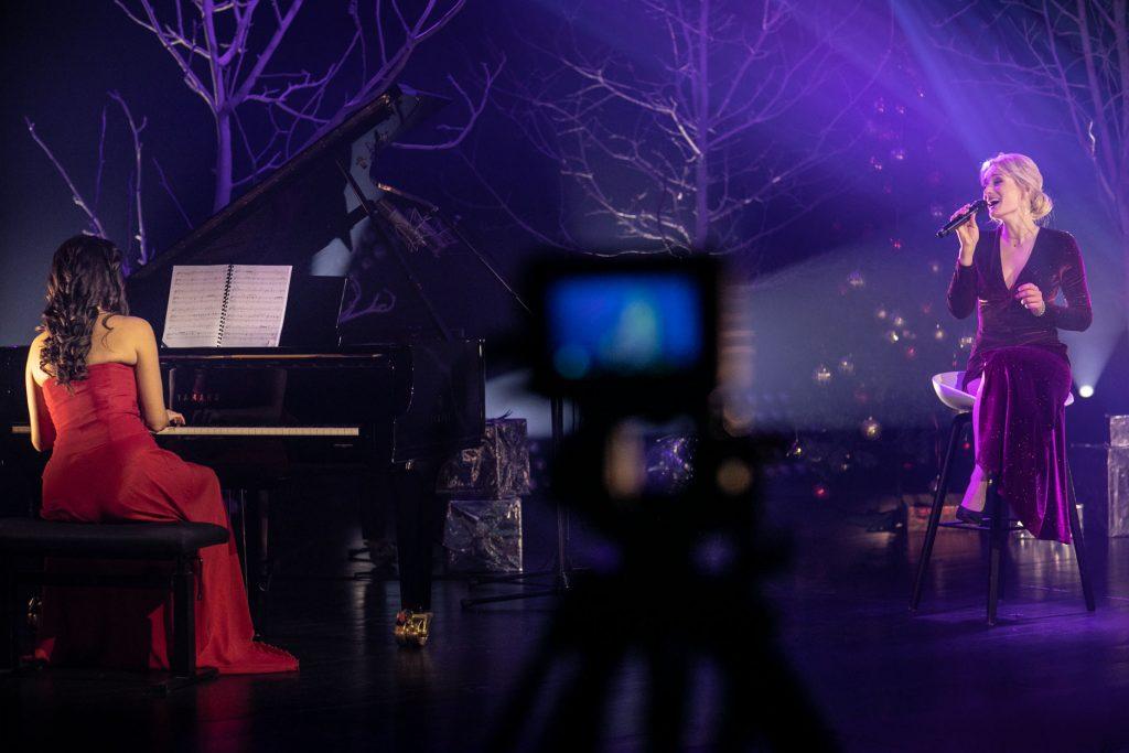 Po lewej stronie , na wysokim krześle siedzi kobieta w długiej sukni śpiewając do mikrofonu. Po lewej stronie kobieta w czerwonej sukni gra na pianinie. Dalej widoczne gałęzie drzew bez liści. Z przodu na środku aparat na statywie.