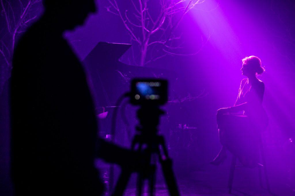 Na scenie półmrok. Kobieta na wysokim krześle siedzi oświetlona smugą różowego światła. Dale stoją drzewa bez liści. Z przodu widoczny cień człowieka stojącego przy statywie z aparatem.