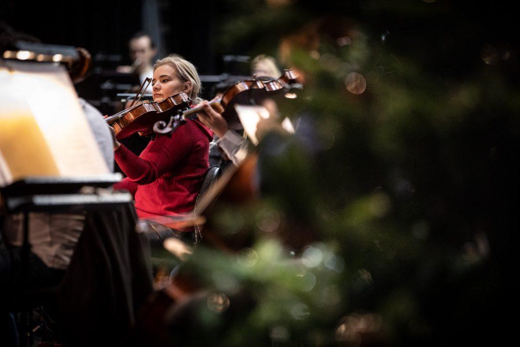 Po prawej stronie zarys choinki. Za nią kobieta grająca na skrzypcach. Wokół widać kilku muzyków orkiestry grających na instrumentach.