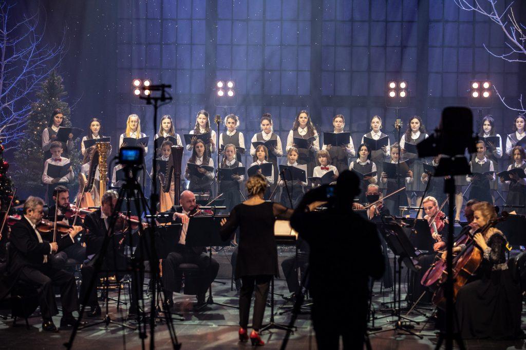 Na scenie gra sekcja smyczkowa Orkiestry Opery i Filharmonii Podlaskiej. Za nimi stoi chór dziecięcy. Wszyscy trzymają otwarte nuty. Z przodu na statywach lampa i aparat.