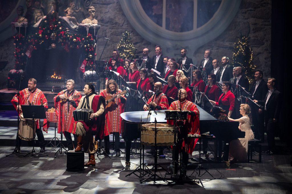 Nagranie do koncertu ''Siła serc''. Z przodu muzycy w strojach argentyńskich. Za nimi, przy fortepianie siedzi kobieta w długiej, jasnej sukni. Dalej stoi część chóru opery. Po lewej stronie widać duży kominek w którym pali się ogień.