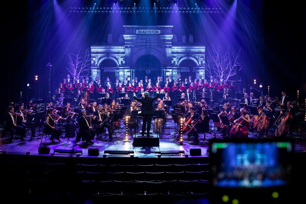 Scena oświetlona na niebiesko. Z przodu widoczne puste krzesła widowni. Na scenie Orkiestra i Chór Opery i Filharmonii Podlaskiej podczas nagrania koncertu. W oddali widoczny budynek z napisem ''Białystok''.