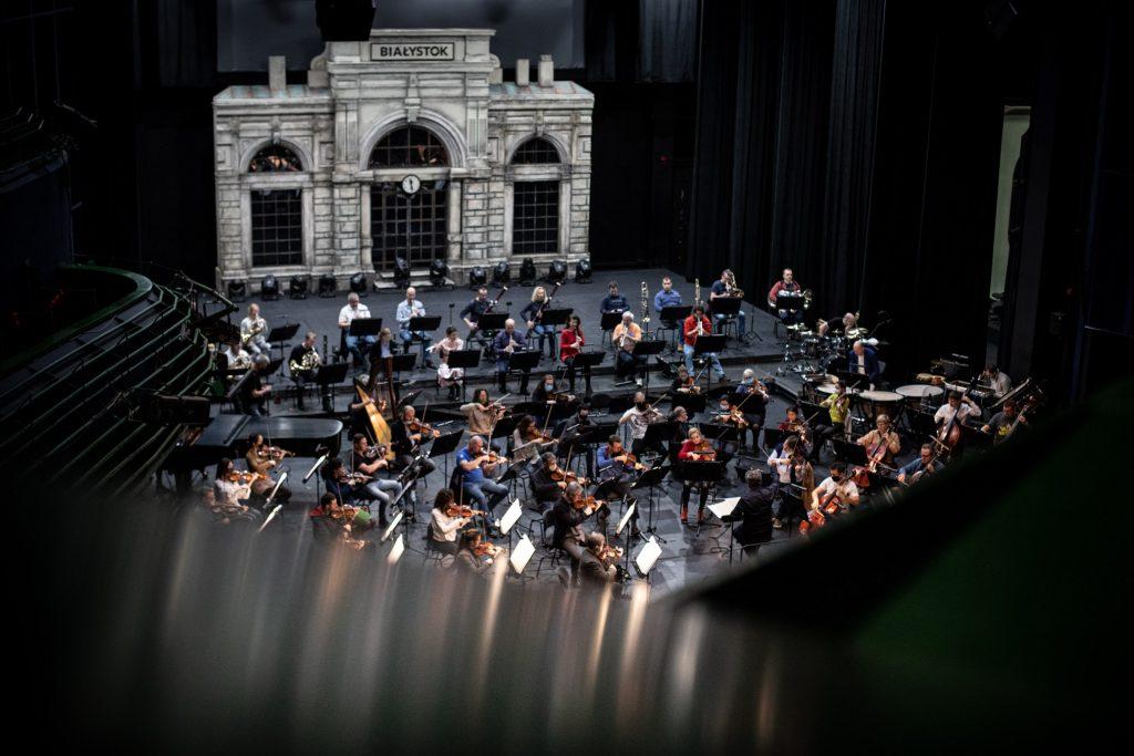 Zdjęcie zrobione z góry. Orkiestra Opery i Filharmonii Podlaskiej podczas próby. Z tyłu scenografia przedstawiająca budynek z dużymi, zaokrąglonymi oknami. U góry napis ''Białystok''.