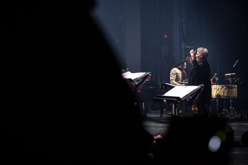 Za pulpitami stoi kierownik chóru z uniesionymi rękoma. Za nią muzycy z zespołu ''Sierra Manta''.