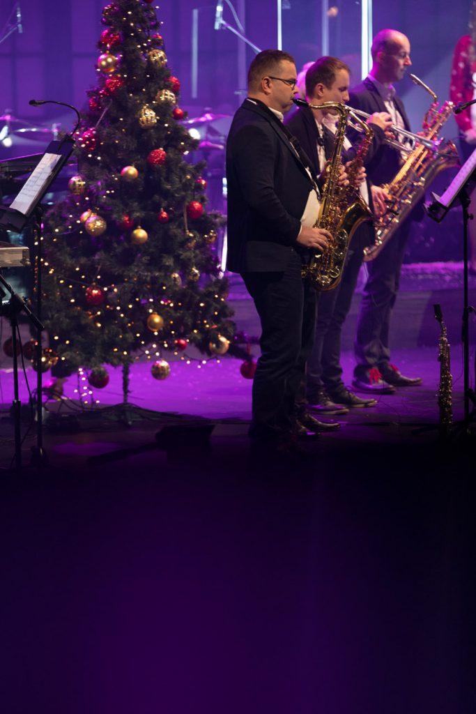 Scena oświetlona fioletowym światłem. Na przodzie stoi czterech mężczyzn, trzech gra na saksofonach, jeden - na trąbce. Za nimi stoi choinka z bombkami.