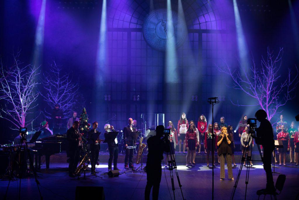Scena oświetlona niebieskim światłem. Na środku stoi solistka. Za nią stoi kilkanaście dziewcząt w swetrach z motywami świątecznymi. Po lewej stronie stoi kilku mężczyzn z instrumentami - saksofonami i trąbką. Przed nimi na środku sceny stoi dwóch mężczyzn przy statywach. Po obydwu stronach sceny gałęzie drzew bez liści.