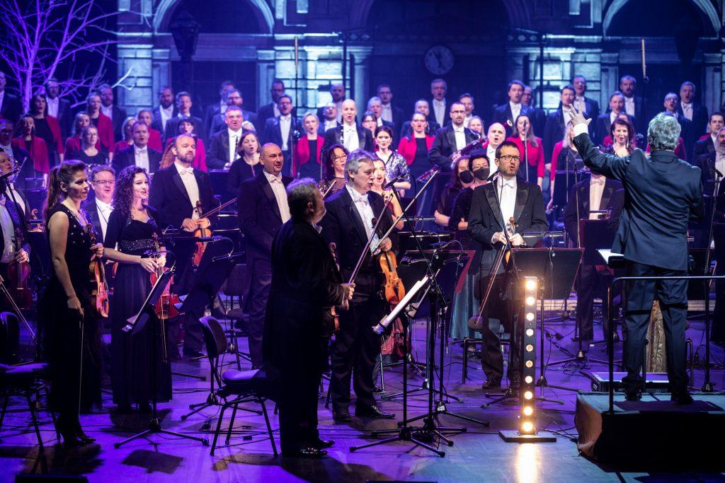 Scena oświetlona na niebiesko. Na scenie stoi Orkiestra i Chór Opery i Filharmonii Podlaskiej. Na środku stoi dyrygent z ręką uniesioną do góry.