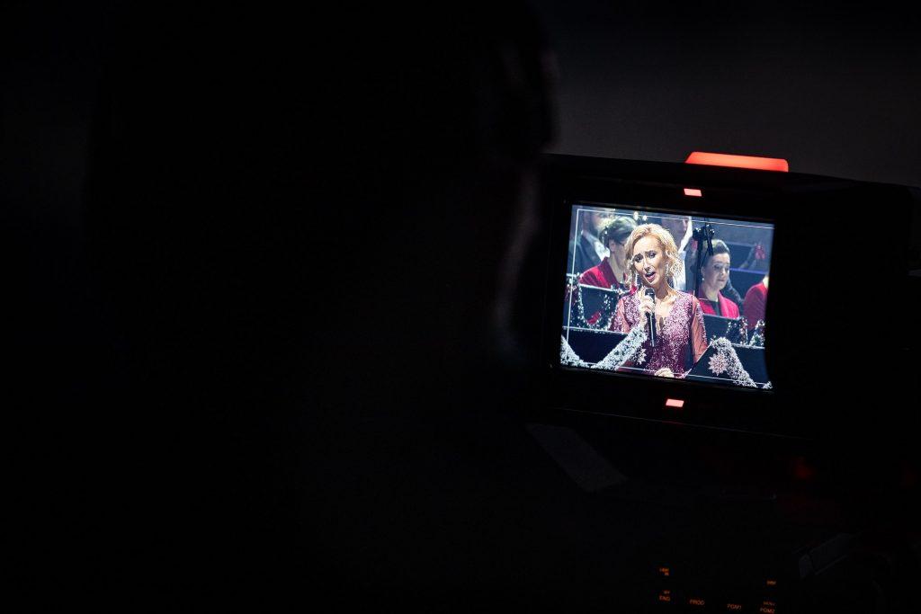 Ekran aparatu na którym wyświetla się solistka z mikrofonem.