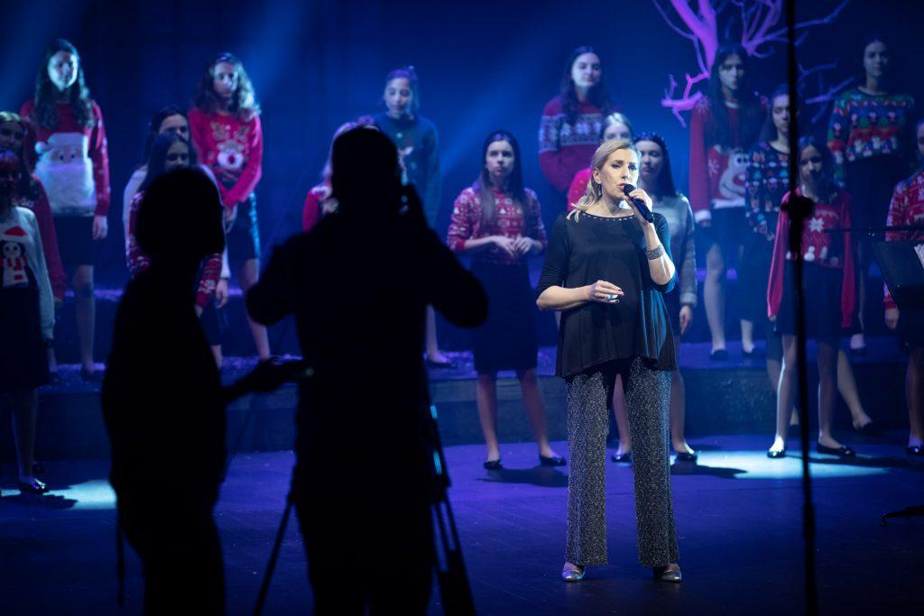 Scena oświetlona niebieskim światłem. Na środku, z mikrofonem stoi kobieta - kierownik Chóru Dziecięcego Opery i Filharmonii Podlaskiej. Za nią kilkanaście dziewcząt w swetrach z motywami świątecznymi. Z przodu widoczne postacie dwóch osób przy statywie.