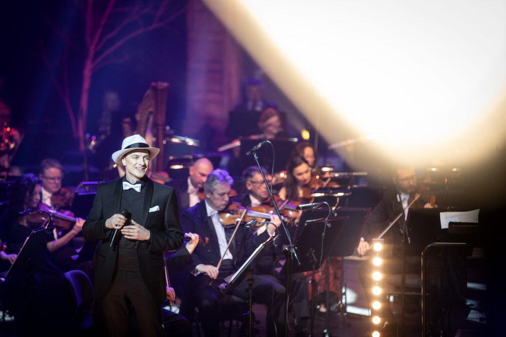 Po lewej stronie stoi mężczyzna w czarnym garniturze i białym kapeluszu. W ręku trzyma mikrofon. Za nim siedzi sekcja smyczkowa orkiestry.