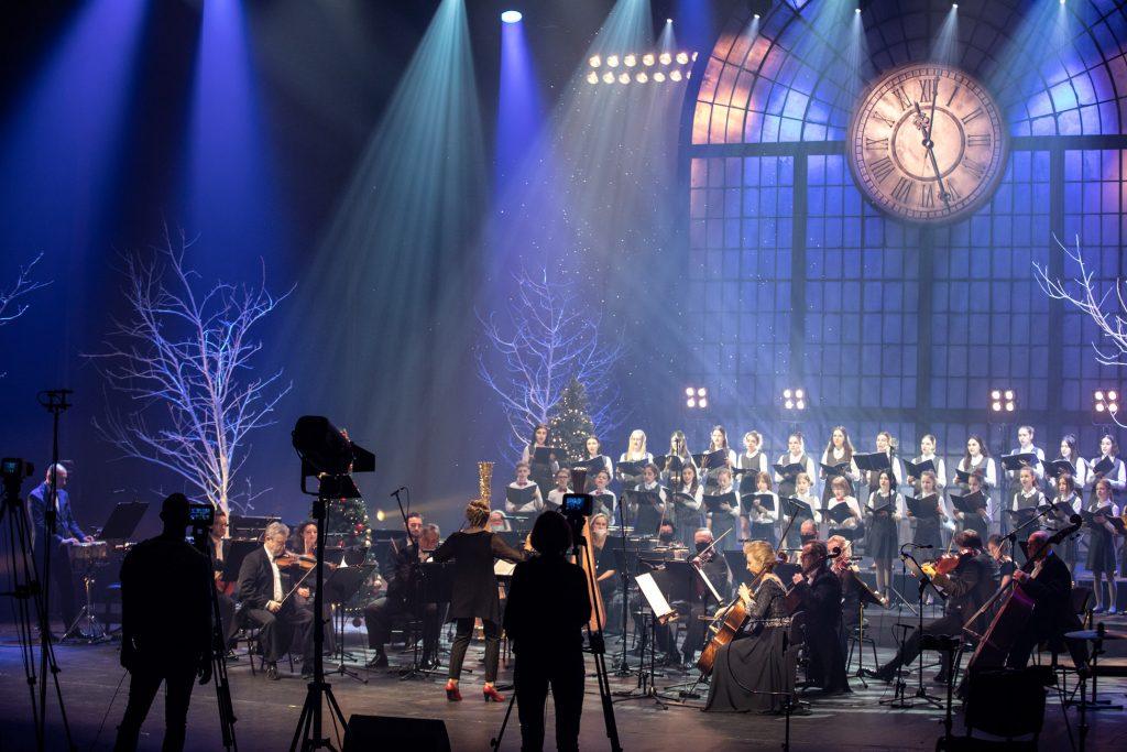 Na scenie opery nagrywany jest koncert '' Radość kolędowania''. Scena oświetlona niebieskim światłem. Z przodu siedzą muzycy z sekcji smyczkowej. Z tyłu, w dwóch rzędach stoi chór dziecięcy. Wszyscy trzymają rozłożone nuty. Po obydwu stronach sceny stoją szare drzewa bez liści. Z przodu przy statywach z aparatami stoi kobieta i mężczyzna.